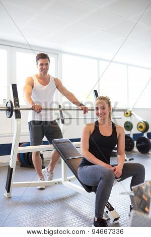 Couple Smiling At Camera After Barbell Exercise