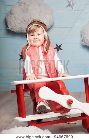 Little girl sitting in wooden toy plane