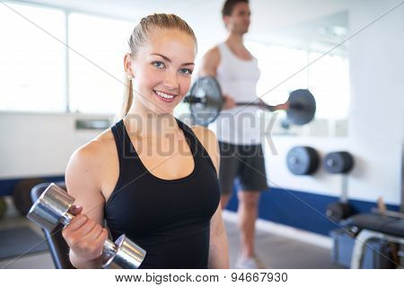 Active Young Female Lifting Dumbbell In The Gym