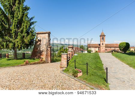 Cobblestone walkway, green lawns and parish church on background under blue sky in Piedmont, Northern Italy.