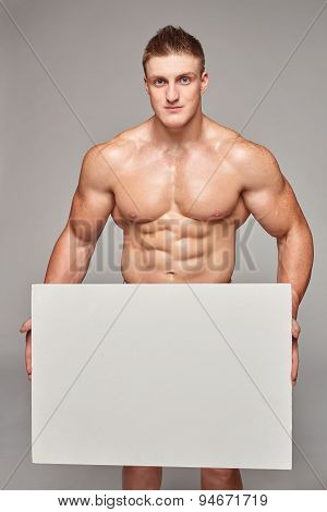 Muscular man holding white banner with copy space