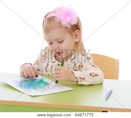 The blonde girl draws a marker on the sheet of paper