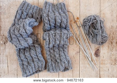 wool grey legwarmers, knitting needles and yarn on wooden background