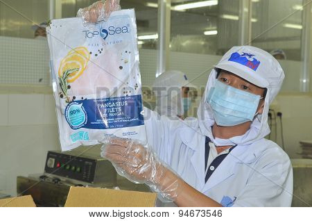 Tien Giang, Vietnam - March 2, 2013: A Worker Is Showing A Certified Pangasius Fish Product In A Sea