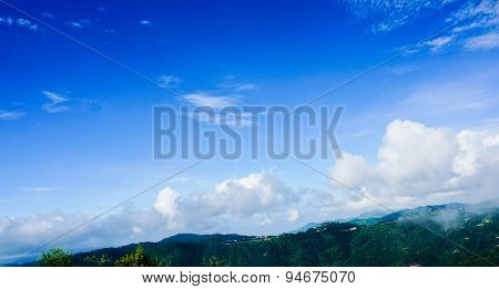 Cumulus Clouds With Hills And Blue Sky