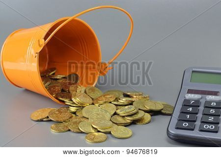 Gold Coins, Calculator And Bucket - Business Concept