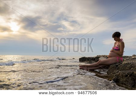 Pregnant Woman In Ninth Month Of Pregnancy Sitting On A Rock By The Sea Cradling Her Swollen Belly