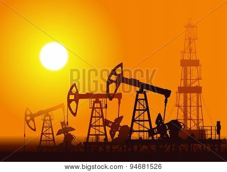 Oil pumps and rig over sunset.