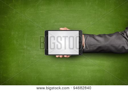 Businessman hand holding tablet front of blackboard