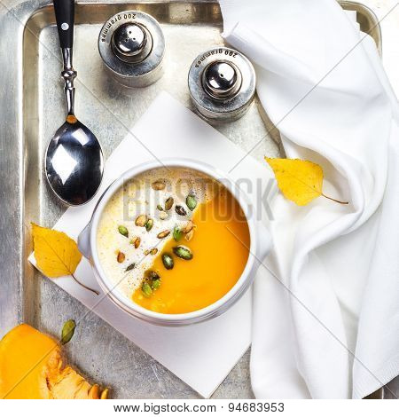 Beautiful Autumn Pumpkin Soup With Cream In A White Bowl With Silverware Over Black Chalk Background