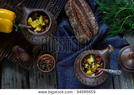 Ceramic Pots With Meat And Vegetables On Wooden Background.