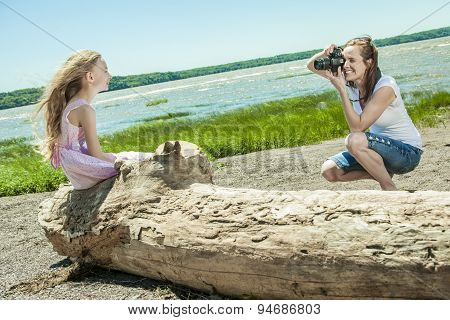 Cheerful mother taking picture of her cute little daughter