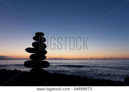sunset at ocean , stone pyramid silhouette