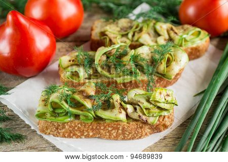 Bruschetta with grilled zucchini and herbs. Soft focus