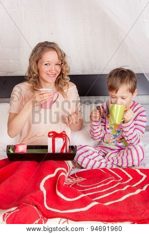 Smiling woman with her child having breakfast