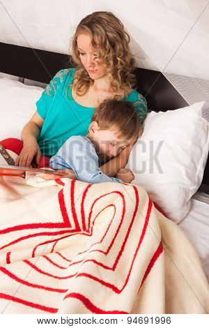 Little son sleeping with his mother in bed