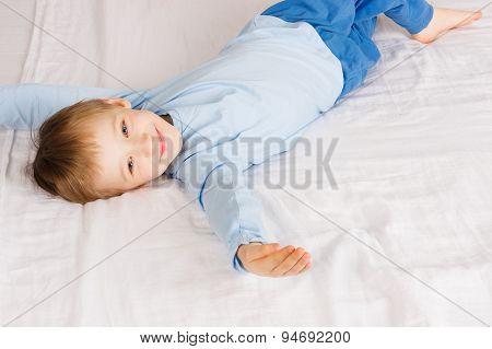 Happy boy laying on big bed