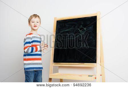 Preschool boy draws a chalk