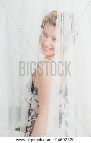 Smiling woman  behind  white transparent textile