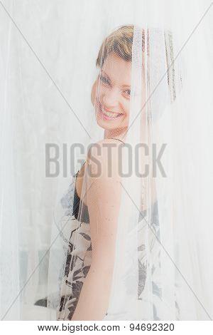 Smiling woman  behind  white transparent textile
