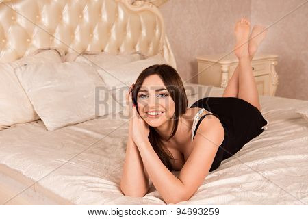 Beautiful Girl In Peignoir Lying On A Luxury Bed With Cushions And Smiling