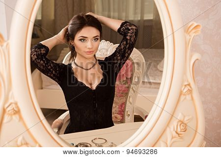 Beautiful Girl Sitting Near A Mirror And Dress Necklace On Her Neck