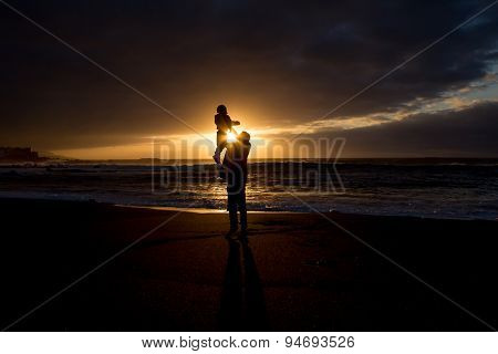 father holds child in front of sunset at ocean