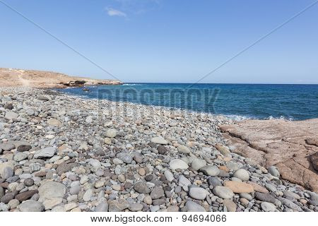 Ocean view - cliff, stones at beach, blue sky, sea and ocean