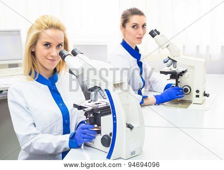 Two medical workers working with microscope