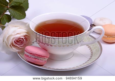 Cup Of Tea With Pink French Macaron And Pastel Rose