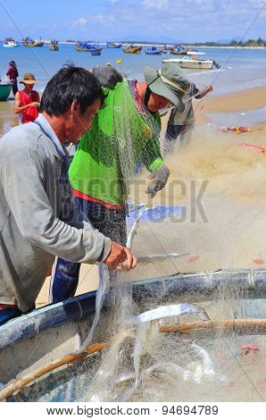 Lagi, Vietnam - February 26, 2012: Local Fishermen Are Removing Fishes From Their Fishing Nets In Th