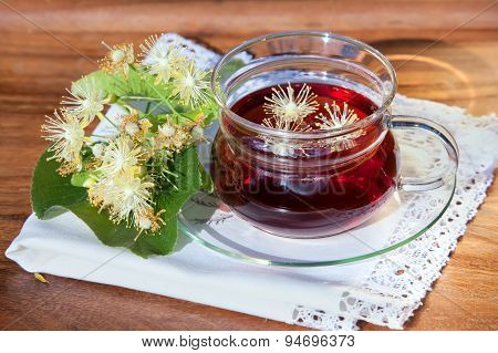 Cup With Linden Tea And Flowers On Wooden Table