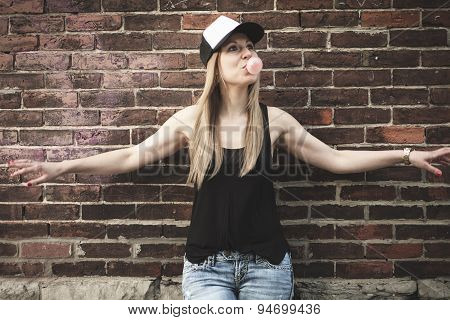 Beautiful modern girl near the brickwall.