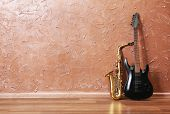 picture of saxophones  - Electric guitar and saxophone on brown wall background - JPG