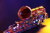 foto of saxophones  - Golden saxophone on purple background - JPG
