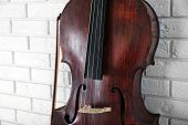 image of cello  - Cello on bricks wall background - JPG