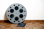 foto of mm  - 35 mm cinema movie roll with clapper on wooden floor and white wall background  - JPG