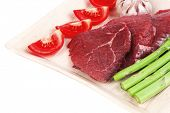 image of white asparagus  - fresh raw beef meat steak fillet on wooden plate with asparagus and tomatoes ready to prepare isolated over white background - JPG
