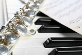 stock photo of flute  - Flute and piano with music sheet close up - JPG