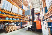 foto of forklift driver  - warehouse worker driver in uniform stacking cardboxes by forklift stacker loader - JPG