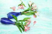 foto of jonquils  - Beautiful alstroemeria in vases on wooden background - JPG