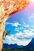 picture of climbing wall  - female rock climber climbs on a rocky wall against a blue cloudy sky - JPG