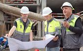 picture of construction  - Two civil engineer and a senior brigadier at construction site are inspecting ongoing construction works according to design drawings - JPG