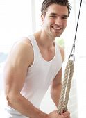 foto of rep  - Close up Muscular Young Guy Smiling at the Camera While Pulling Down Pulley Device Inside the Fitness Gym - JPG