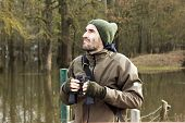 picture of observed  - Man in jacket and binoculars standing on shore and observing river - JPG