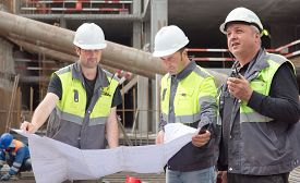 foto of personal safety  - Two civil engineers and a senior foreman at construction site are inspecting ongoing construction works according to design drawings - JPG