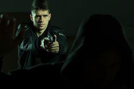foto of pistols  - Image of a handsome confident cop pointing pistol at criminal - JPG