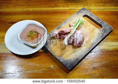 dog premium wet food in tray and fresh raw pork on chop block