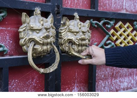 hand holding a door handle, close up