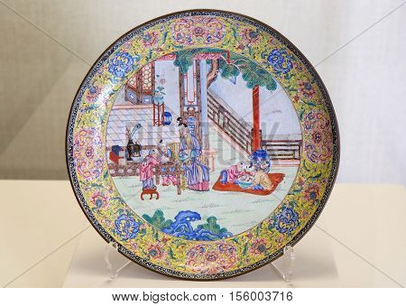 BEIJING - FEBRUARY 23: Painted enamel round plate with designs of beatiful ladies and five children from Qing Dynasty in Forbidden City, Beijing, China, February 23, 2016.